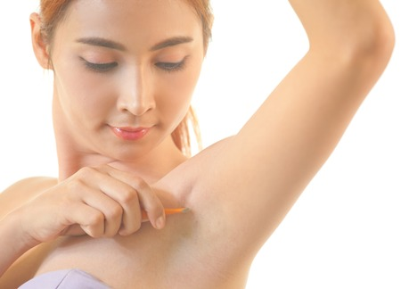 Young asian woman shaving armpit with razor isolated on white background photo