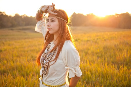 Hippie woman posing in golden field on sunset photo