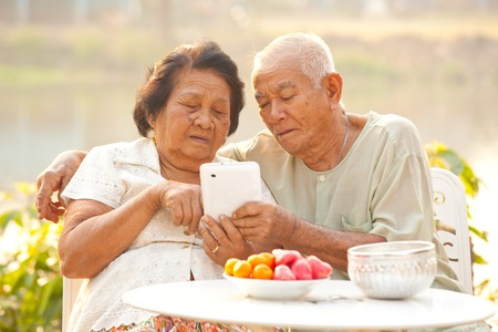 Happy asian senior couple using the tablet on outdoor background photo