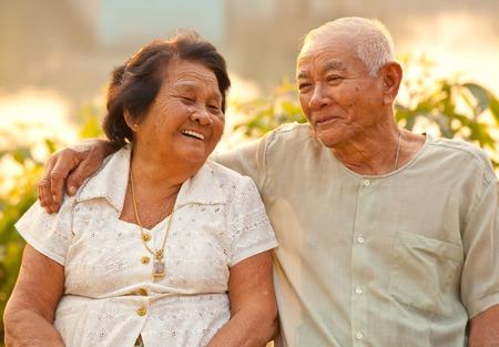 Gelukkig Aziatische Senior paar zitten buiten op zonsondergang