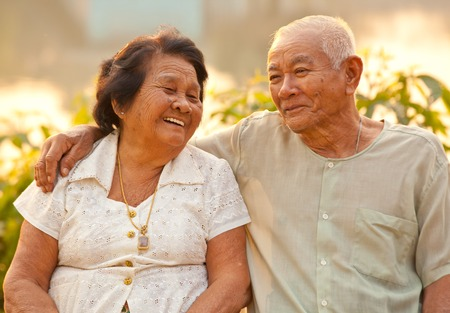 Happy Asian Senior couple sitting outdoors on sunset Stock fotó