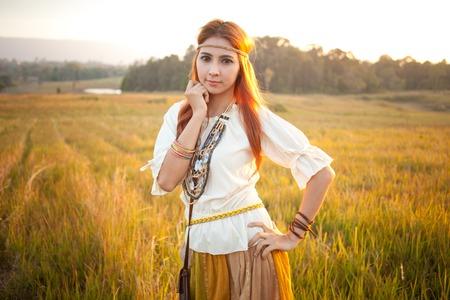 mujer hippie: Mujer del Hippie que presenta en campo de oro en la puesta del sol