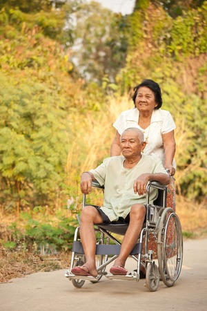 Asian senior woman pushing her disabled hasband on wheelchair photo