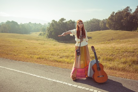 Hippie girl with guitar hitchhiking on countryside road photo