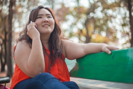 Happy fatty asian woman using mobile phone outdoor in a park Imagens - 26579405