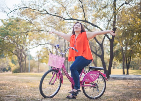 Happy fatty asian woman outstretched with bicycle outdoor in a park photo