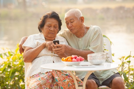 Happy asian senior couple using the mobile phone on outdoor background photo