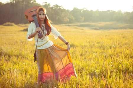 Hippie woman walking in golden field with acoustic guitar photo