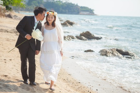 sea flowers: Happy young asian couple in love outdoor on the beach Stock Photo