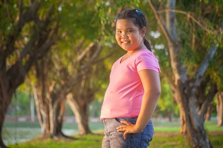 Portrait asian fat girl in the park on sunset Stock Photo