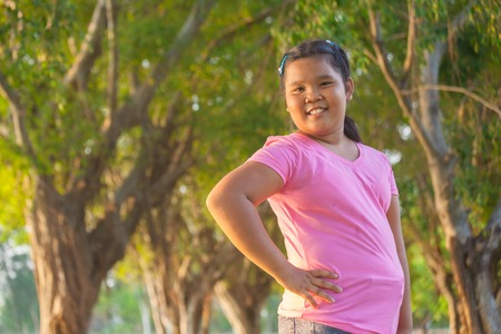 fat kid: Portrait asian fat girl in the park on sunset Stock Photo