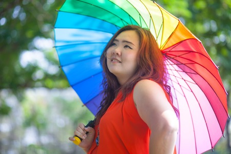 plus size woman: Happy fatty asian woman with umbrella outdoor in a park Stock Photo