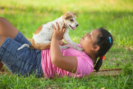 little asian girls and puppy in the garden photo