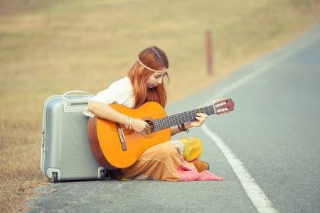 mujer hippie: Mujer Hippie tocando m�sica en el camino rural