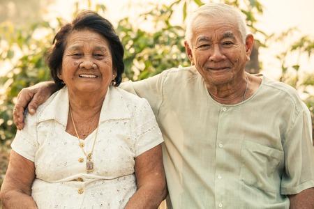 Happy Asian Senior couple sitting outdoors on sunset Stock Photo