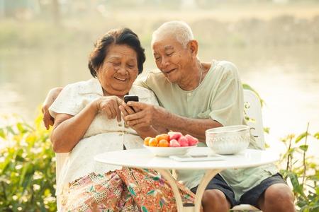 landline: Felice asiatiche coppia senior utilizzando il telefono cellulare su sfondo esterna Archivio Fotografico