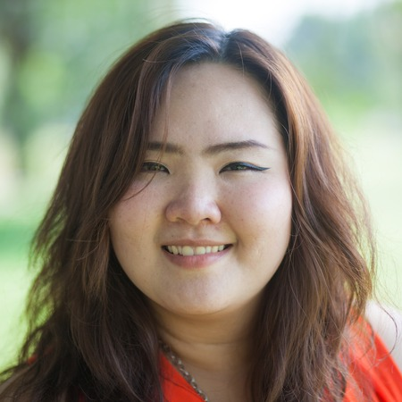 Close up of happy fatty asian woman outdoor in a park photo