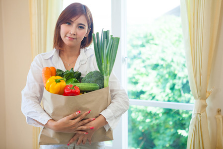 Happy Young Asian Woman with vegetables in shopping bag photo