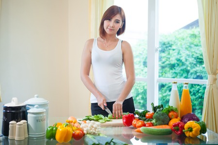 Happy asian woman cooking vegetables green salad in the kitchen photo