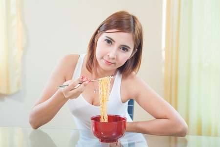 Young Asian girl eating ramen noodles using chopsticks photo
