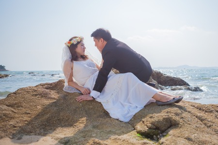 Happy young asian couple in love outdoor on the beach photo
