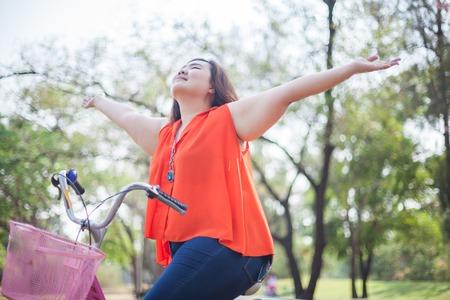 Felice grassa donna asiatica disteso all'aperto con bicicletta in un parco