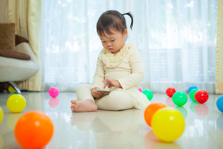 mobile telephones: Happy little asian girl using mobile phone in the home