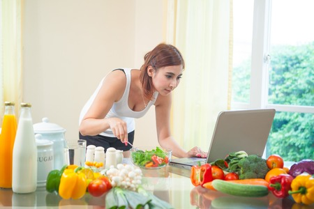 cook house: Young asian woman looking for a recipe on the internet in kitchen