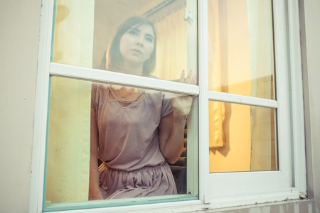 despair: Beautiful young asian woman is sad at the window