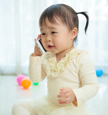 Portrait of pretty asian little girl talking on mobile phone Standard-Bild