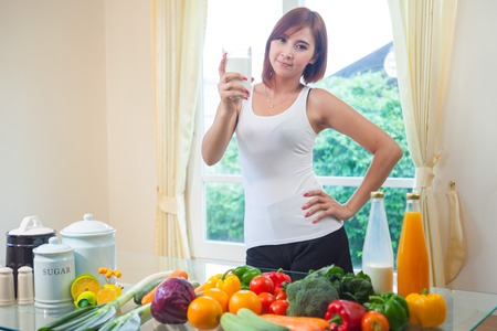 Young asian woman drinking milk in kitchen Stock Photo