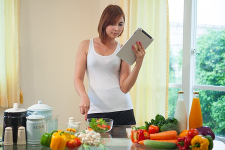Young asian woman In Kitchen Following Recipe On Digital Tablet Stock Photo - 29103266
