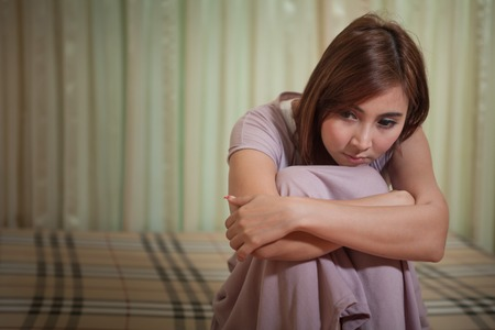 Asian sad woman sitting on the bed in bedroom Stock Photo