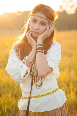 mujer hippie: Mujer Hippie posando en campo de oro en la puesta del sol