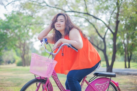 Happy fatty asian woman posing with bicycle outdoor in a park photo