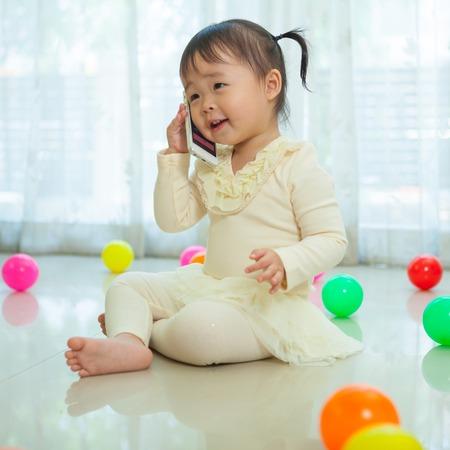 Portrait of pretty asian little girl talking on mobile phone photo