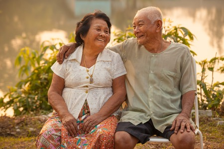 Happy Asian Senior couple sitting outdoors on sunset Banque d'images
