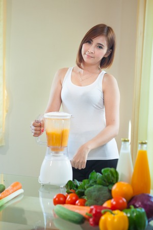 Beautiful Young Asian Woman Making Fruit Smoothie in Blender photo