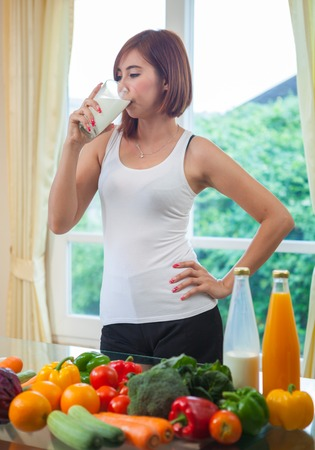 Young asian woman drinking milk in kitchen photo