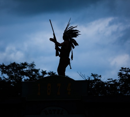 indian warrior: Silhouette of American Indian warrior man with feather headdress and tomahawk