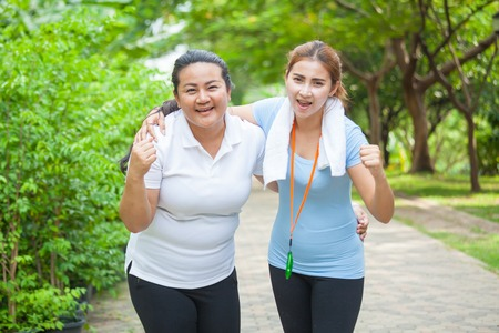 Portrait of two fit young women smiling in a bright outdoor