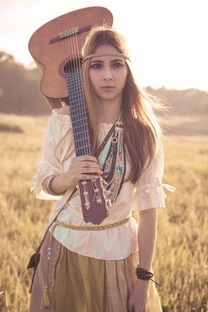 mujer hippie: Mujer del hippie que recorre en campo de oro con la guitarra ac�stica Foto de archivo