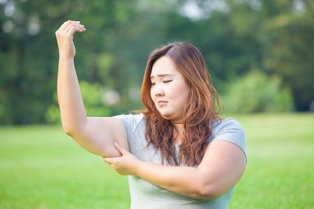 mujeres gordas: Mujer joven grasa asiático que controla su grasa del brazo