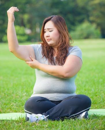 Young asian fat woman checking her arm fat Standard-Bild
