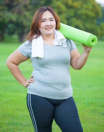 obeso: Bastante grasa mujer asi�tica va a funcionar con su estera de yoga Foto de archivo