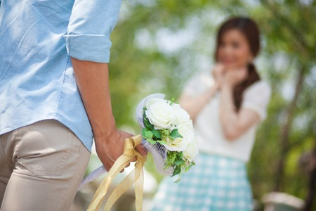 Man ready to give flowers to girlfriend in the park