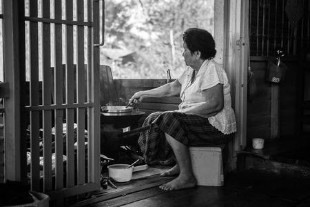 台所で料理をしてアジアの年配の女性の黒と白のイメージ