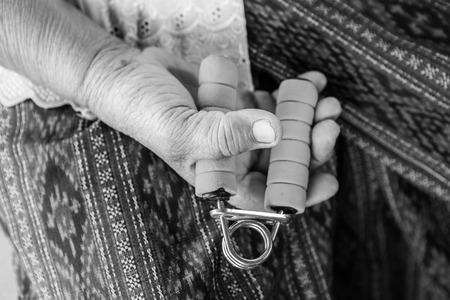 hand grip: Black and white image of Senior asian woman exercise sport hand grip equipment