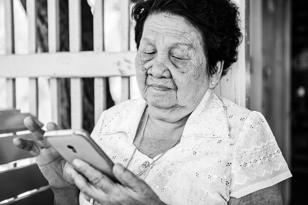 Black and white image of Senior asian woman  with smart phone photo