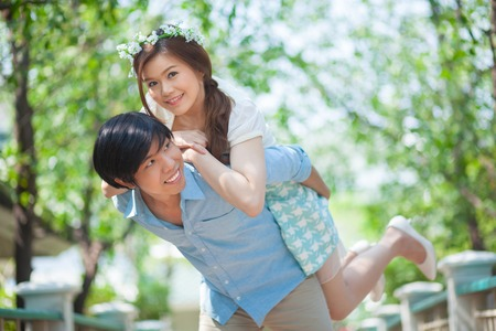 piggy back: Young asian man giving a piggy back to his girlfriend in the park